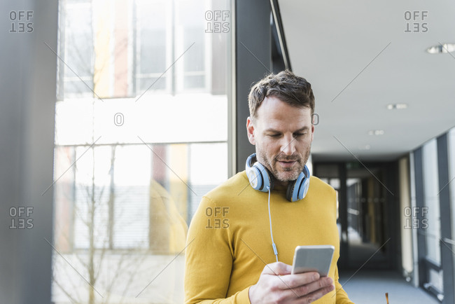 Casual businessman in office using smartphone