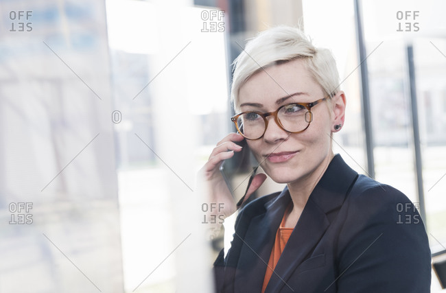 Portrait of confident businesswoman on cell phone in office