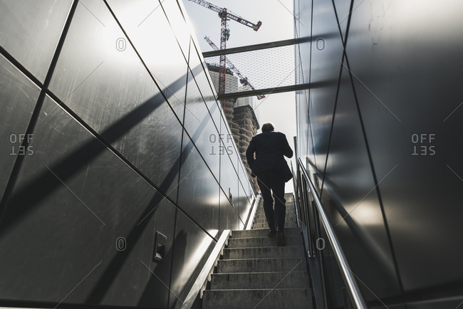 Businessman walking on staircase in the city