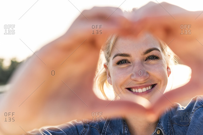 Woman making heart shape with hands and fingers
