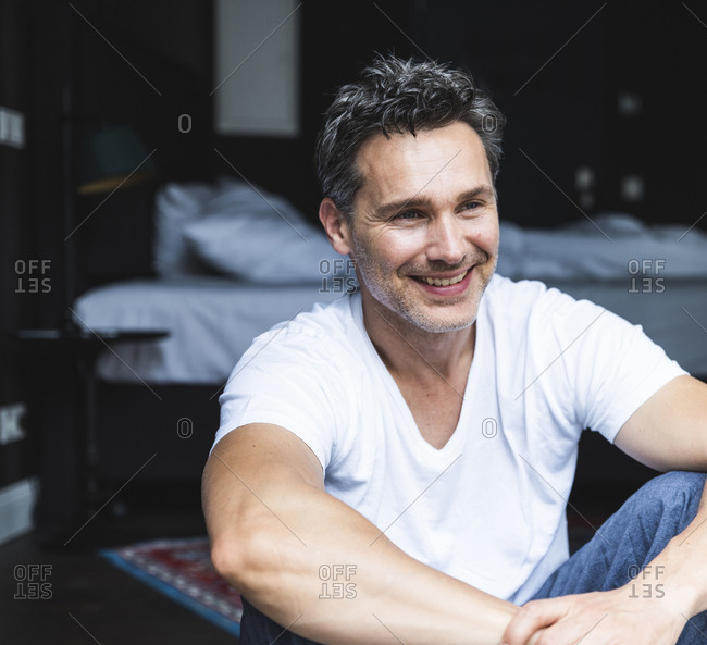Smiling man in pajama at home sitting down