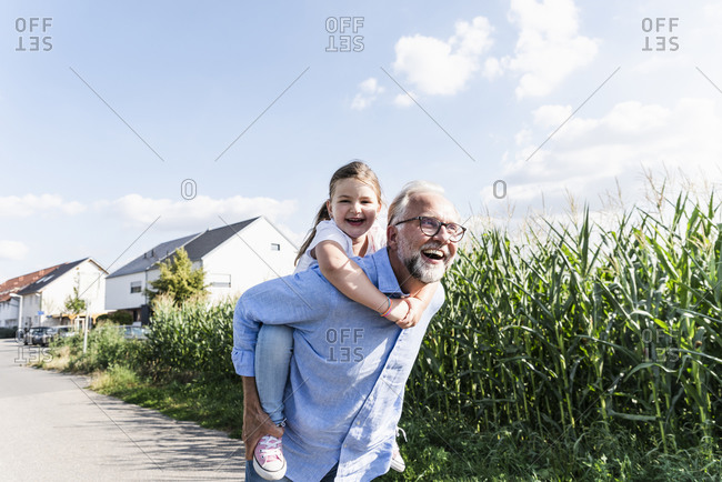 Grandfather carrying granddaughter piggyback - Offset
