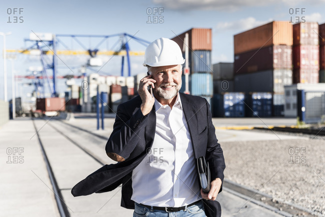 Businessman at cargo harbor- wearing safety helmet- using smartphone