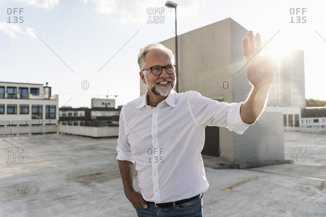 Mature man standing on roof of a high-rise building- catching the sun