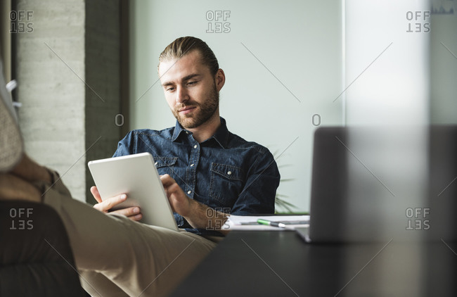 Businessman sitting in office with feet up using tablet