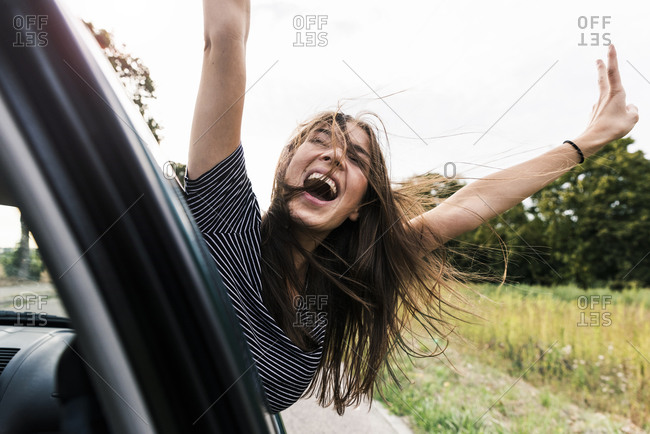 Carefree young woman leaning out of car window screaming