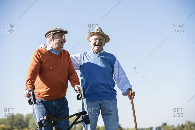 Old friends taking a stroll in the fields with walking stick and wheeled walker- talking about old times