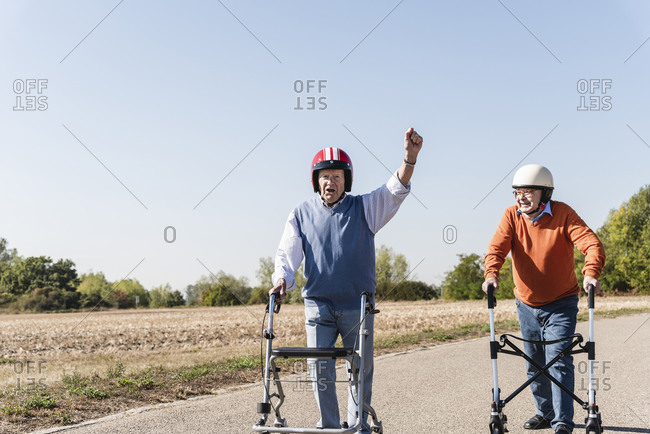 Two old friends wearing safety helmets- competing in a wheeled walker race