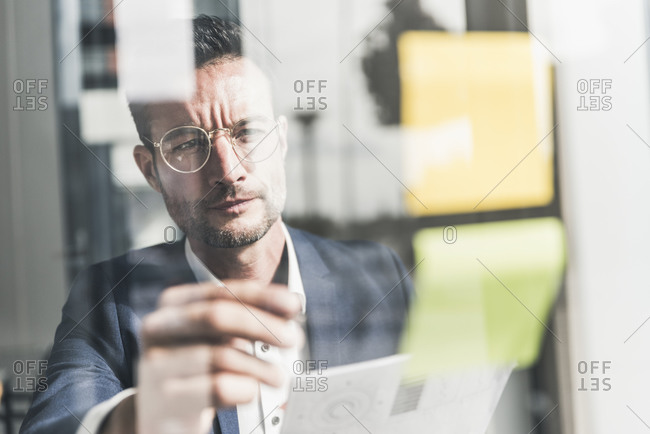 Businessman brainstorming in office- using sticky notes