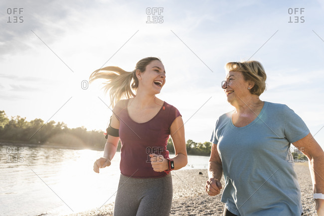 Granddaughter and grandmother having fun- jogging together at the river