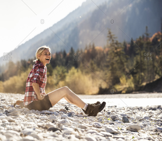 Austria- Alps- laughing woman on a hiking trip having a break at a brook