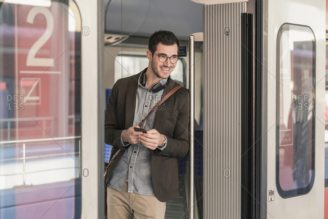 Smiling young man with cell phone in commuter train