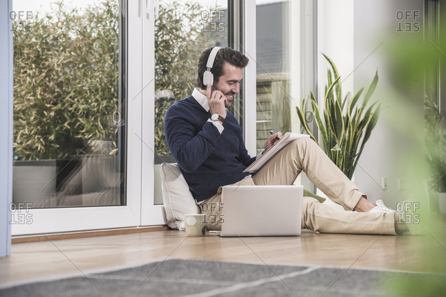 Young man sitting in living room- leaning on window- working with laptop- taking notes