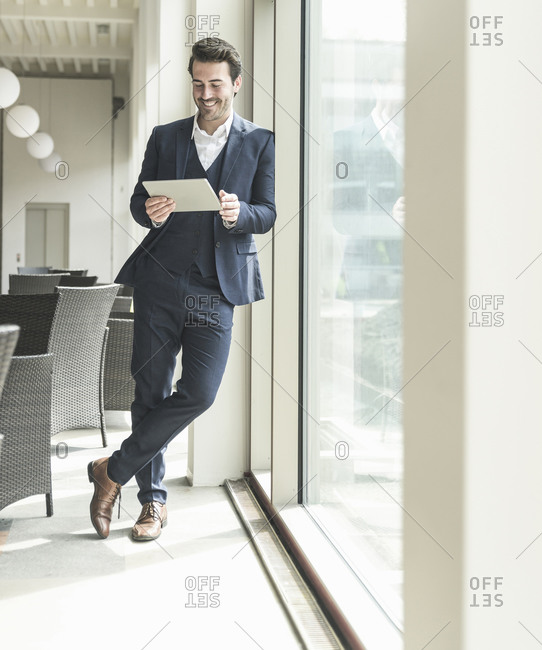 Young businessman standing in office building- using digital tablet- leaning on window