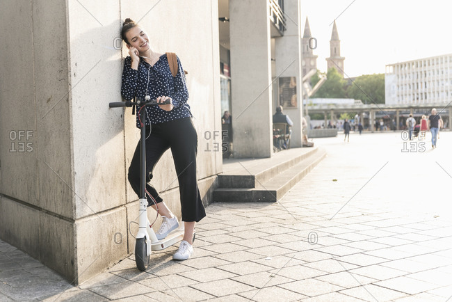 Smiling young woman with electric scooter and earphones having a break in the city