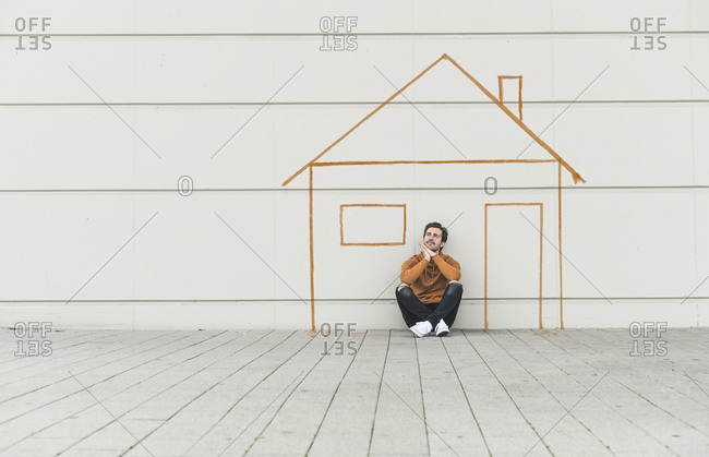 Digital composite of young man sitting at a wall with a house