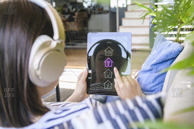 Young woman with tablet that has smart home control functions and headphones