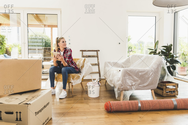 Woman moving into new home using tablet