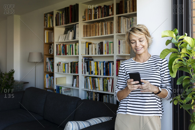 Smiling mature woman standing at the window in living room at home using smartphone
