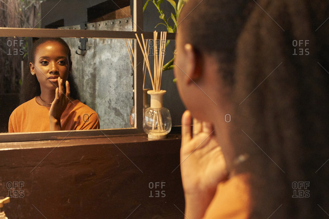 Young woman looking in bathroom mirror