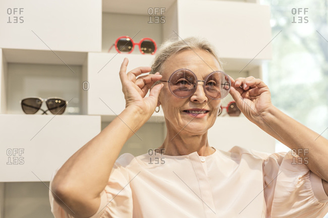 Smiling senior woman trying on sunglasses in a boutique