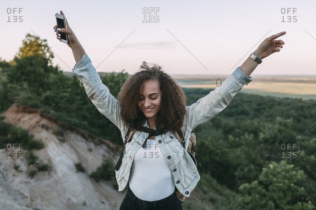 Happy teenage girl with smartphone and backpack in nature