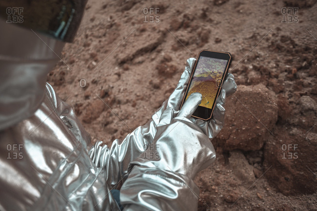 Spaceman examining new planet- using smartphone