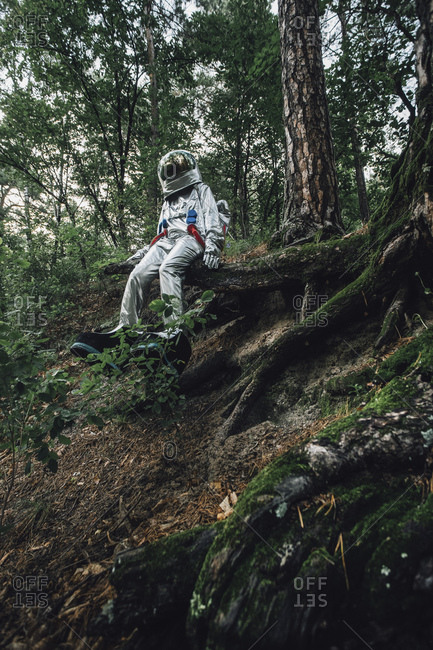 Spaceman exploring nature- sitting on tree roots