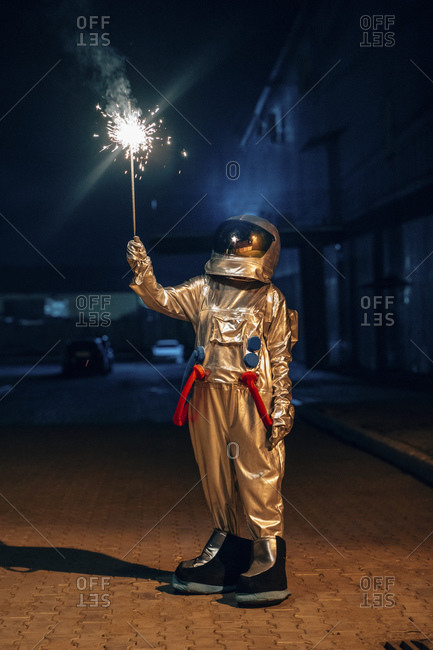 Spaceman standing outdoors at night holding sparkler