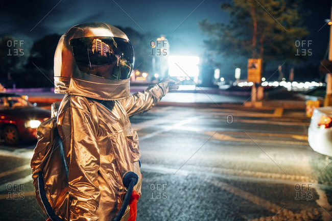 Spaceman on a street in the city at night pointing at shining projection screen