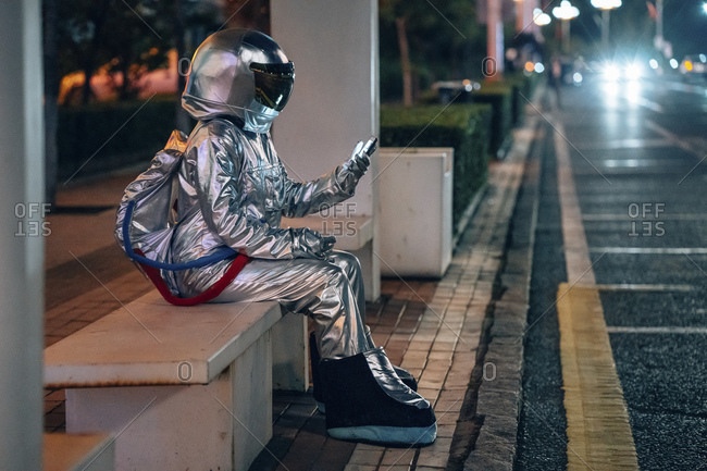 Spaceman sitting on bench at a bus stop at night holding cell phone