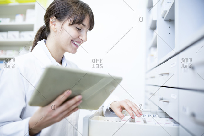 Smiling pharmacist with tablet at cabinet in pharmacy