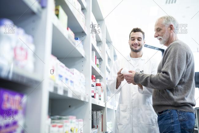 Pharmacist advising customer in pharmacy