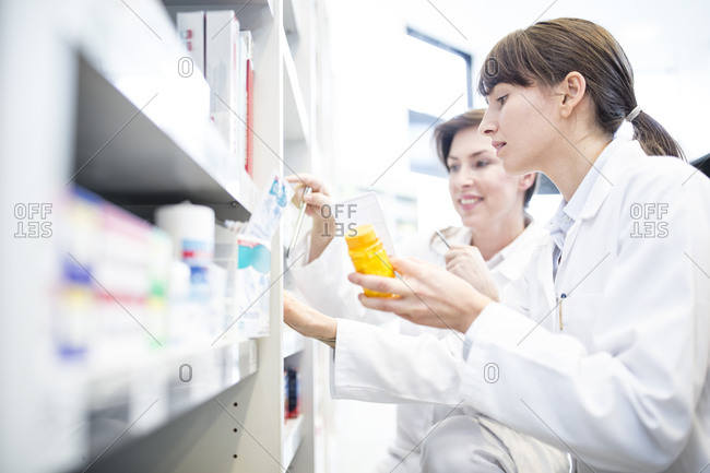 Two pharmacists with pill box at shelf in pharmacy