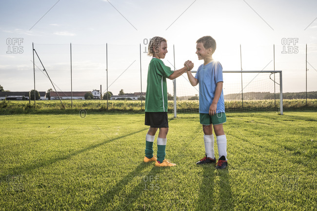 Smiling young football players shaking hands on football ground