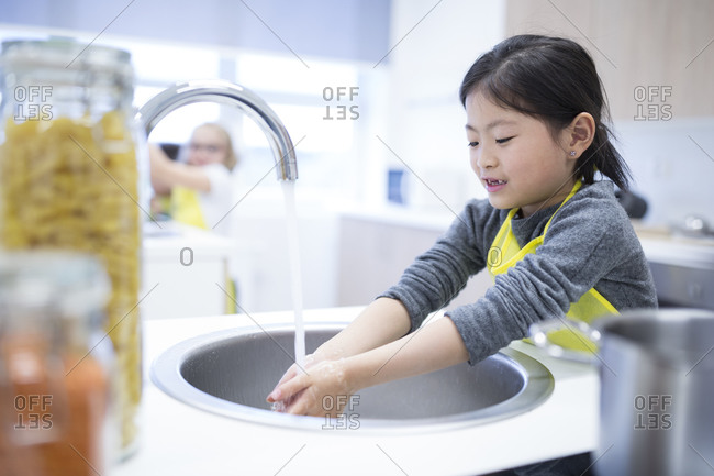 Schoolgirl washing her hands in cooking class