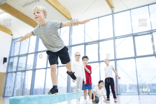 Schoolboy balancing on balance beam in gym class