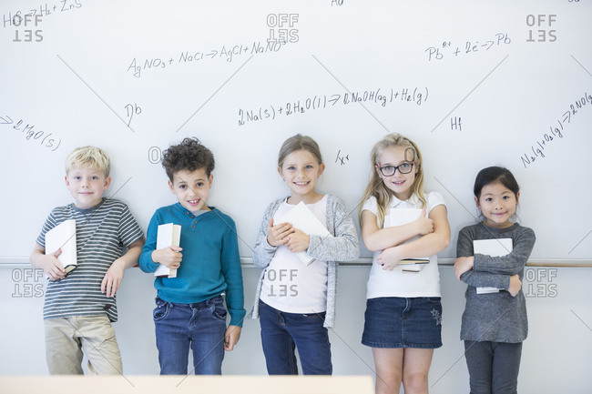 Portrait of smiling pupils standing at whiteboard with formulas in class