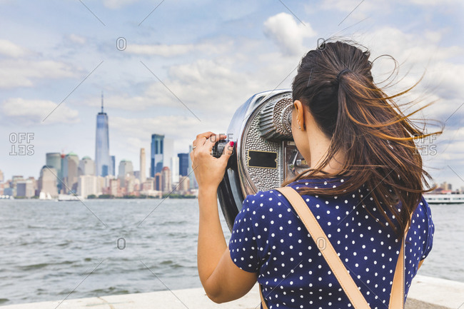 USA- New York- woman looking at Manhattan skyline with coin-operated binoculars