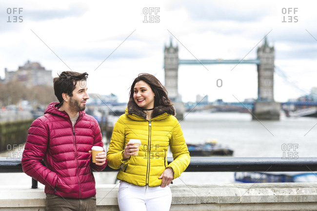 UK- London- couple with coffee to go standing on bridge over the Thames