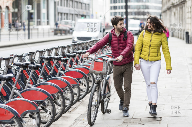 UK- London- young couple with bicycle from bike share stand walking in city