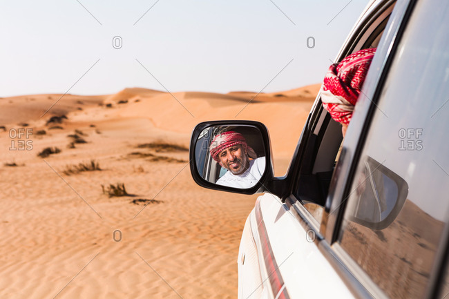 Bedouin looking in his car mirror- Sultanate Of Oman- Wahiba Sands