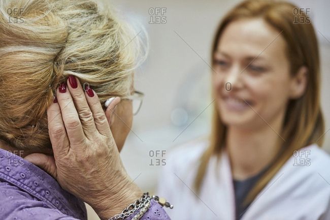 Female doctor and senior woman with hearing aid