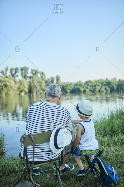 Back view of grandfather and grandson fishing together at lakeshore