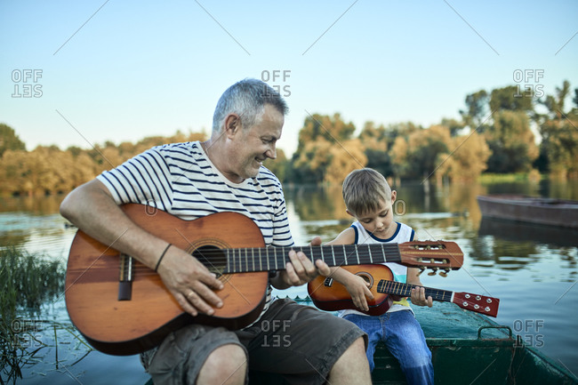 Grandfather teaching grandson playing guitar