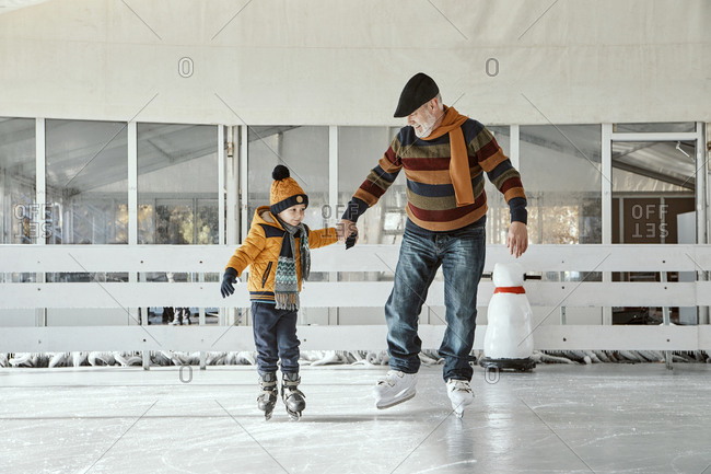 Grandfather and grandson on the ice rink- ice skating