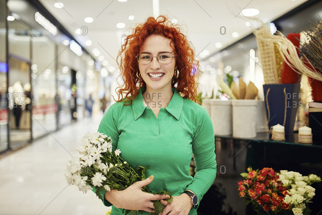 Portrait of smiling florist holding bunch of flowers in flower shop
