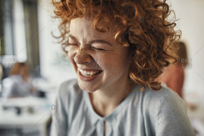 Portrait of a laughing businesswoman with closed eyes in office