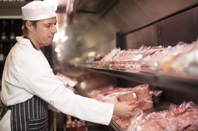 Butcher packing meat for display