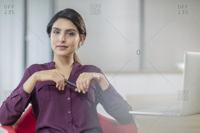 Portrait of confident businesswoman with laptop in office